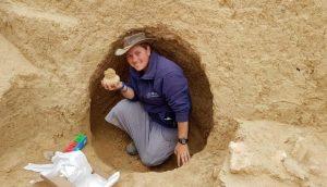 הארכיאולוגית שירה בלוך מחזיקה פך בן 2000 שנמצא בחפירה. צילום: רשות העתיקות
